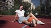 sportos : Cute teen brunette girl with a basketball ball looking at the camera sitting on the basketball court outdoors. Concept of sport, power, competition, active lifestyle. Sports and recreation.