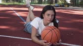 sportos : Adorable teen brunette girl with a basketball ball looking at the camera lying on the basketball court outdoors. Concept of sport, power, competition, active lifestyle. Sports and recreation.