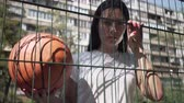 sportos : Pretty brunette woman holding basketball ball looking at the camera standing behind the mesh fence at the basketball court. Concept of sport, competition, active lifestyle. Sports and recreation.
