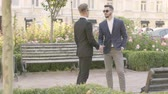 bank employee : Two young partners meeting in the park and shaking hands. Confident manager meets his client outdoors. Business meeting, business relationship.