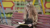 okumak : Cute teen girl is reading a book while sitting on a bench outdoors.