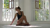 yogi : Young red-haired healthy caucasian woman practicing yoga on the mat in the white large room. Young woman in sports clothing exercising on fitness indoors. Stock Footage