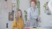 konular : Red-haired mother and her daughter admiring a piece of beautiful fabric. Seamstress works at workshop. Happy loving family. Stok Video