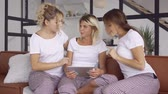 giymek : Three happy girlfriends in the same pajamas spending time together at home with a tablet. Women addicted to gadgets. Hen-party, pajama party. Girls have fun indoors Stok Video