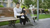 incentivo : Handsome guy sits on the bench in the park listening to music on his cellphone. Crutches and skateboard are nearby. Active life of disabled person. Motivation, normal life, never give up