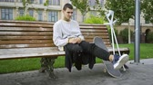 インセンティブ : Young man sitting on the bench in the park while listening to music on his cellphone then taking crutches and skateboard and riding away. Active life of disabled person. Motivation, normal life 動画素材
