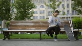 incentivo : Attractive young man sitting on the bench in the park listening to music on his cellphone then taking crutches and skateboard and riding away. Active life of disabled person. Motivation, normal life
