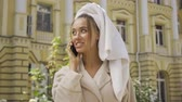 busy : Portrait of cute smiling jou young woman in bathrobe with towel on head talking by cellphone on the street. Confident girl enjoying a beautiful day in the city