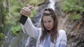 broderie : Adorable young woman in embroidered shirt taking selfie standing in front of waterfall. Connection with wild nature. Leisure outdoors, active lifestyle Vidéos Libres De Droits