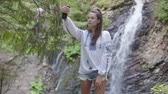 broderie : Cute young woman in embroidered shirt taking selfie standing in front of waterfall. Connection with wild nature. Leisure outdoors, active lifestyle