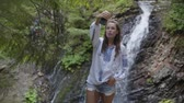 broderie : Cute young woman in embroidered shirt taking selfie standing in front of waterfall. Connection with wild nature. Leisure outdoors, active lifestyle. Slow motion