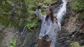 broderie : Pretty young woman in embroidered shirt taking selfie standing in front of waterfall. Connection with wild nature. Leisure outdoors, active lifestyle. Slow motion Vidéos Libres De Droits