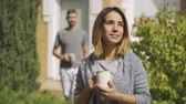 samen bouwen : Attractive caucasian woman standing with the cup of tea in the foreground, her husband coming from behind and kissing her cheek. Young family together at the house. Summertime Stockvideo