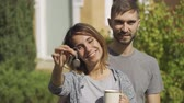 samen bouwen : Portrait of attractive caucasian woman with cup of tea and handsome man standing in front of a large house. The wife showing house key and smiling. Ownership