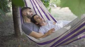 függőágy : Young caucasian man and woman lying in hammock in the garden relaxing together. Loving couple together outdoors. Summertime leisure