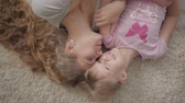 rolle : Top view of happy caucasian mother and her little daughter laying on fluffy carpet at home. Woman and girl resting at home and smiling. Happy family. Videos
