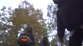 stabbing : Man and two young women in Halloween costumes looking down on the victim with serious scary faces in autumn park. The girl showing big knife, going to kill, the guy holding pumpkin. Bottom view Stock Footage