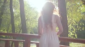 멀리보고 : Back view of redhead caucasian woman in light white dress standing in the autumn park in sunrays. Young girl spending last warm days outdoors. 무비클립