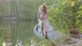 nymphe : Charming redhead caucasian woman in white long dress sitting on the bank of the lake reading the book in dark red cover. Lovely fairy girl spending last warm autumn days outdoors.
