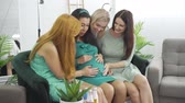 bevalling : Four smiling caucasian girls in light dresses caressing belly of the expectant woman. Cute young women spending time with their pregnant friend at the pre-bith party. Stockvideo