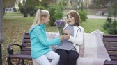 gratulálok : Young caucasian teen in casual clothes giving wildflowers to the brunette adult woman sitting on the bench in the autumn park. Granddaughter surprising her grandma.