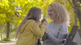 dát : Two little cute caucasian sisters giving their mom flowers and kissing her. Pretty blond curly woman enjoying holidays with her lovely daughters in the autumn park.