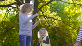 soap bubbles : Young blonde woman staying in the sunny park and blowing soap bubbles. Her two little pretty daughters running around trying to catch bubbles. Joyful caucasian family having fun on weekends. Stock Footage