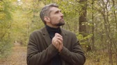 yaprak döken : Close-up of a handsome Caucasian man with grey hair standing in the forest. Guy in casual clothes blowing on his hands and rubbing them.. Stok Video