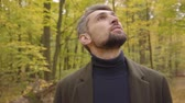 yaprak döken : Close-up of a handsome adult Caucasian man standing in the forest and looking up. Guy in casual clothes enjoying calm quiet autumn day alone. Stok Video