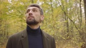 yaprak döken : Close-up of a handsome Caucasian man with grey hair and brown eyes standing in the forest and looking up. Guy in casual clothes enjoying calm quiet autumn day alone.