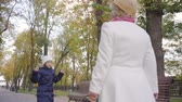 beco : Little Caucasian girl in white hat and warm blue coat jumping in front of her grandmother walking along the alley. Mature woman in beige cloche hat and white coat spending time with her granddaughter Stock Footage