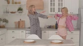 パジャマ : Two beautiful blonde Caucasian girls dancing at the kitchen. Girls in having pajama party at home.