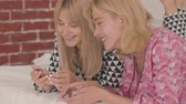 パジャマ : Side view of two young blonde Caucasian girls in pajamas laying on the white soft bed and looking at the smartphone. Happy smiling women having pajama party at home. 動画素材