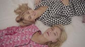 feestzaal : Top view of blonde Caucasian grey-eyed girls laying on the bed and smiling. Women in pajamas resting in the bedroom at home. Stockvideo