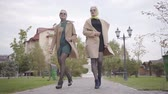 фрак : Two elegant mature Caucasian female friends in beige coats, short dresses and sunglasses walking in the city park. Charming adult women spending autumn day together outdoors. Стоковые видеозаписи