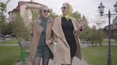 фрак : Two mature Caucasian women in beige coats, short dresses and sunglasses walking in the city park and talking. Charming adult female friends travelling together.