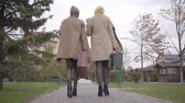 фрак : Back view of two mature Caucasian women in elegant clothes and sunglasses walking in the city park with travel bags and talking. Charming adult female friends travelling together after retirement.