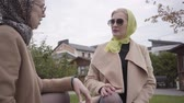 фрак : Close-up of two adult Caucasian women wearing headscarves and sunglasses sitting on the bench and talking. Elegant mature female friends spending time together outdoors.