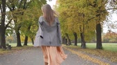 verificador : Back view of a slim Caucasian woman in checkered jacket and mustard dress walking in the autumn park. Young girl strolling along the road and turning to look into the camera. Stock Footage