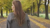 фрак : Confident Caucasian brunette girl looking around and walking away along the road. Nice smiling woman in checkered jacket strolling in the autumn park.