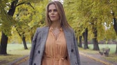 gęś : Close-up of a confident Caucasian girl in mustard dress and checkered jacket walking along the road. Pretty brunette woman strolling in the autumn park on weekends.