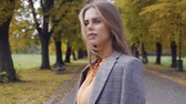 фрак : Nice brunette girl standing in the autumn park and looking around. Beautiful Caucasian woman in checkered jacket spending time outdoors. Camera moving around the model.