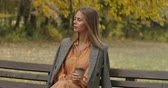 фрак : Beautiful Caucasian woman sitting on the bench in the autumn park with a cup of coffee. Attractive girl shaking her long brown hair and looking away. Cinema 4k footage ProRes HQ. Стоковые видеозаписи