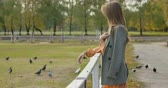 фрак : Side view of an attractive Caucasian woman with long brown hair standing next to the corral in the autumn park. Pretty girl in checkered jacket resting outdoors. Cinema 4k footage ProRes HQ. Стоковые видеозаписи