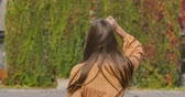 gęś : Back view of a young Caucasian woman in mustard dress with goose foot print. Wind blowing long brown hair of elegant girl. Cinema 4k footage ProRes HQ.