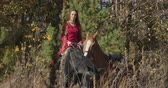 postroj : Portrait of young Caucasian female equestrian sitting on back of black horse and holding halter of brown stallion. Professional jockey spending sunny autumn day in forest. Cinema 4k footage ProRes HQ