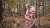 örök : Portrait of happy Caucasian retired couple standing in sunlight in the autumn forest or park and hugging. Mature European family spending sunny evening outdoors. Aging together, eternal love concept.