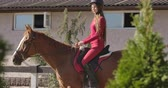 saddle : Brunette Caucasian female equestrian sitting on the back of graceful brown horse. Portrait of a jockey in pink clothes and horse riding helmet in the saddle. Cinema 4k footage ProRes HQ.