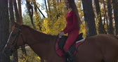 saddle : Side view of Caucasian girl with long brown hair in pink clothes sitting on brown horseback in autumn forest. Young female equestrian resting with graceful animal outdoors. Cinema 4k footage ProRes HQ