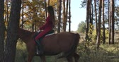 saddle : Professinal Caucasian female equestrian dressed in pink clothes riding brown horse in autumn forest. Young female equestrian resting with her animal friend outdoors. Cinema 4k footage ProRes HQ.